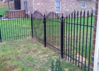 This decorative wrought iron fence has a scalloped top and spears.